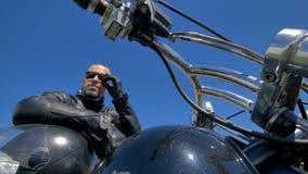 Ένας ποδηλάτης, μοτοσυκλετιστής στηρίζεται τα χέρια σε ένα κράνος και τις αφές τα γυαλιά ηλίου του 4K απόθεμα βίντεο