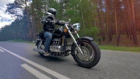 Ένας ποδηλάτης που οδηγά μια μοτοσικλέτα που φορά τα μαύρα ενδύματα και το κράνος απόθεμα βίντεο
