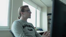 Ένας προγραμματιστής με τα γυαλιά και ένα γκρίζο σακάκι με μια επιγραφή αντι-ηρώων ανατρέχει φιλμ μικρού μήκους