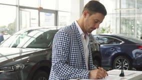 Ένας προσεκτικός αγοραστής υπογράφει μια σύμβαση για την αγορά ενός αυτοκινήτου στοκ φωτογραφία