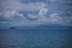 Ένας πυκνά νεφελώδης ουρανός με τη θύελλα καλύπτει Πανοραμική άποψη των βουνών στο μακρινό νησί στοκ φωτογραφίες
