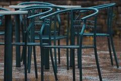 Ένας πυροβολισμός σε διάφορες πράσινες καρέκλες μετάλλων στη βροχή στοκ εικόνες