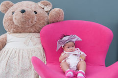 Ένας πυροβολισμός ενός χαριτωμένου κοριτσάκι με πορφυρό headband και μεγάλος teddy αντέχουν κοισμένος και παίζοντας στη ρόδινες κ Στοκ Εικόνες