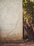 Ένας ραγισμένος τοίχος με wheelbarrows και τα εργαλεία που κλίνουν ενάντια σε το μέσα στοκ εικόνες