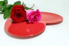 Ένας ρόδινος και ένας κόκκινος αυξήθηκε πάνω από το λαμπρό κόκκινο διαμορφωμένο καρδιά πιάτο στοκ φωτογραφία με δικαίωμα ελεύθερης χρήσης