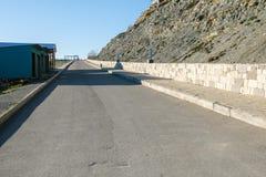Ένας δρόμος ασφάλτου ανεβαίνει δίπλα στο βουνό στοκ φωτογραφίες