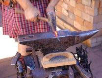 Ένας σιδηρουργός σφυρηλατεί το κόκκινο - καυτό μέταλλο στα ξίφη (στενός επάνω) Στοκ Εικόνα