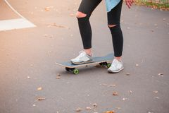 Ένας σκέιτερ κοριτσιών στέκεται με ένα πόδι skateboard σε ένα πάρκο σαλαχιών Στοκ φωτογραφίες με δικαίωμα ελεύθερης χρήσης