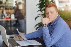 Ένας σκεπτικός νέος redhead επιχειρηματίας που φορά την επίσημη συνεδρίαση πουκάμισων στον πίνακα με το lap-top και τα έγγραφα στ Στοκ Εικόνες