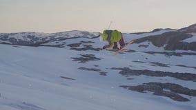 Ένας σκιέρ που εκτελεί τη συναρπαστική ακροβατική επίδειξη σε σε αργή κίνηση, κάνοντας σκι στα βουνά χιονιού φιλμ μικρού μήκους