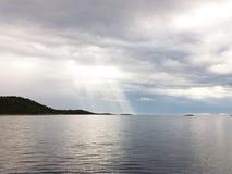 Ένας σκοτεινός θυελλώδης ουρανός επάνω από τη θάλασσα Κορυφογραμμές βουνών επάνω από το νερό στοκ εικόνα με δικαίωμα ελεύθερης χρήσης