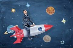 Ένας σοβαρός επιχειρηματίας οδηγά έναν ασημένιο και κόκκινο πύραυλο μεταξύ των σχεδίων των πλανητών και των αστεριών Στοκ Φωτογραφίες