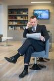Ένας σοβαρός επιχειρηματίας που διαβάζει μια εφημερίδα Στοκ Φωτογραφίες