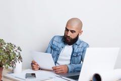 Ένας σοβαρός φαλακρός επιχειρηματίας με την παχιά μαύρη γενειάδα και mustache τη φθορά του πουκάμισου Jean που είναι πολυάσχολου  Στοκ Εικόνες