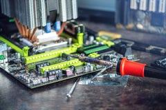 Ένας σπασμένος υπολογιστής και ένας συγκολλώντας σίδηρος στην υπηρεσία Έννοια του μικροτσίπ υψηλής τεχνολογίας και επισκευής Στοκ Φωτογραφία