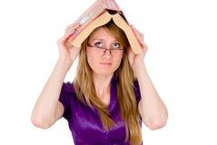 Ένας σπουδαστής κοριτσιών κρατά ένα λεξικό στο κεφάλι στοκ φωτογραφίες με δικαίωμα ελεύθερης χρήσης