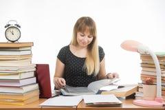 Ένας σπουδαστής σε έναν πίνακα που ρυπαίνεται με τα βιβλία στη βιβλιοθήκη με ένα χαμόγελο, που γυρίζει τις σελίδες σε έναν φάκελλ Στοκ εικόνα με δικαίωμα ελεύθερης χρήσης