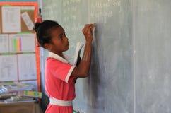 Ένας σπουδαστής Fijian γράφει στον πίνακα Στοκ Εικόνες