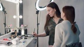 Ένας στιλίστας που κάνει makeup την όμορφη γυναίκα στο στούντιο απόθεμα βίντεο
