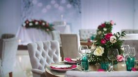 Ένας στρογγυλός ξύλινος πίνακας που διακοσμείται με τις floral ρυθμίσεις που γίνονται από τα άσπρα πιάτα με τις ρόδινες πετσέτες  απόθεμα βίντεο