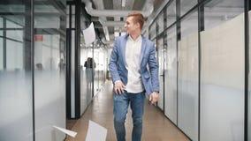 Ένας συγκινημένος επιχειρηματίας που χορεύει στο διάδρομο γραφείων και που ρίχνει τα έγγραφα στον αέρα απόθεμα βίντεο