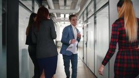 Ένας συγκινημένος επιχειρηματίας που χορεύει στο διάδρομο γραφείων, την υπόδειξη στους συναδέλφους του και το χαμόγελο απόθεμα βίντεο