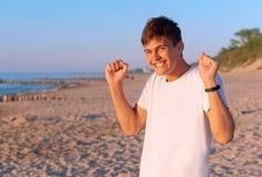 Ένας συμπαθητικός νεαρός άνδρας είναι ευτυχής στην παραλία, ένας νεαρός άνδρας θαυμάζει στην παραλία, το αγόρι είναι πολύ ευτυχές Στοκ Εικόνες