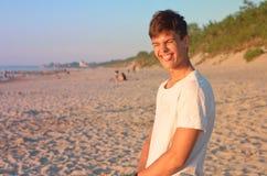 Ένας συμπαθητικός νεαρός άνδρας είναι ευτυχής στην παραλία, ένας νεαρός άνδρας θαυμάζει στην παραλία, το αγόρι είναι πολύ ευτυχές Στοκ Φωτογραφίες