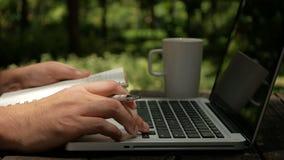 Ένας σχεδιαστής ατόμων freelancer που φαίνεται ιδέες σχετικά με το lap-top και που γράφει στο σημειωματάριο στον κήπο φιλμ μικρού μήκους