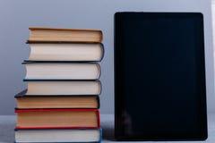 Ένας σωρός των βιβλίων και μιας ταμπλέτας σε μια γκρίζα ανασκόπηση Η έννοια της εκπαίδευσης foreground στοκ φωτογραφία με δικαίωμα ελεύθερης χρήσης