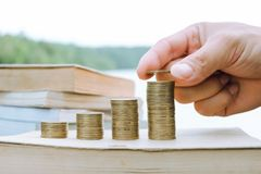 Ένας σωρός των βιβλίων με τα νομίσματα αύξησης χρημάτων στοκ φωτογραφία