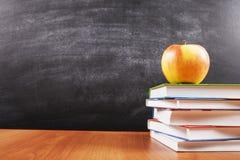 Ένας σωρός των βιβλίων και ένα μήλο στο υπόβαθρο πινάκων με το copyspace για το κείμενό σας, σχέδιο Πίσω στη σχολική έννοια για Στοκ Εικόνες