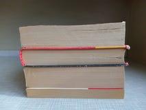 Ένας σωρός των βιβλίων σε μια γκρίζα επιτραπέζια πλάγια όψη του κατώτατου σημείου των βιβλίων Στοκ Φωτογραφία