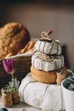 Ένας σωρός των κεφαλιών τυριών σε ένα έγγραφο, έπειτα ένα τεμαχισμένο τυρί, καλάθι του ψωμιού και σταφύλια, βουλώματα κρασιού και Στοκ εικόνες με δικαίωμα ελεύθερης χρήσης