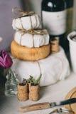 Ένας σωρός των κεφαλιών τυριών σε ένα έγγραφο, έπειτα ένα τεμαχισμένο τυρί, καλάθι του ψωμιού και σταφύλια, βουλώματα κρασιού και Στοκ Φωτογραφίες