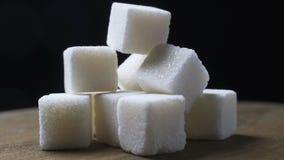 Ένας σωρός των κομματιών ζάχαρης περιστρέφεται σε ένα μαύρο κλίμα απόθεμα βίντεο
