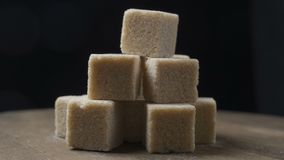 Ένας σωρός των κομματιών ζάχαρης περιστρέφεται σε ένα μαύρο κλίμα φιλμ μικρού μήκους