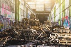 Ένας σωρός των παλαιών ξύλινων παλετών σε μια εγκαταλειμμένη αποθήκη εμπορευμάτων Στοκ Φωτογραφία