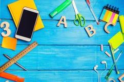 Ένας σωρός των σχολικών προμηθειών σε ένα μπλε ξύλινο επιτραπέζιο υπόβαθρο Η έννοια της εκπαιδευτικής διαδικασίας, που κάνει την  στοκ φωτογραφία με δικαίωμα ελεύθερης χρήσης