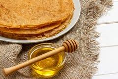 Ένας σωρός των τηγανιτών, μέλι, για τον εορτασμό του καρναβαλιού Λεπτές τηγανίτες για τις τηγανίτες και το μέλι Maslenitsa προγευ Στοκ φωτογραφία με δικαίωμα ελεύθερης χρήσης