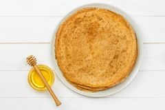 Ένας σωρός των τηγανιτών, μέλι, για τον εορτασμό του καρναβαλιού Λεπτές τηγανίτες για τις τηγανίτες και το μέλι Maslenitsa προγευ Στοκ Φωτογραφία