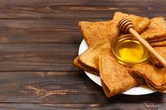 Ένας σωρός των τηγανιτών, μέλι, για τον εορτασμό του καρναβαλιού Λεπτές τηγανίτες για τις τηγανίτες και το μέλι Maslenitsa προγευ Στοκ Εικόνες