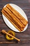 Ένας σωρός των τηγανιτών, μέλι, για τον εορτασμό του καρναβαλιού Λεπτές τηγανίτες για τις τηγανίτες και το μέλι Maslenitsa προγευ Στοκ εικόνα με δικαίωμα ελεύθερης χρήσης