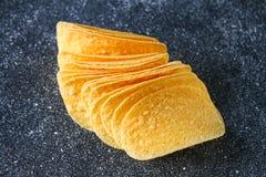 Ένας σωρός των τριζάτων τσιπ σε έναν γκρίζο σκοτεινό πίνακα snack στοκ εικόνες