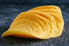 Ένας σωρός των τριζάτων τσιπ σε έναν γκρίζο σκοτεινό πίνακα snack στοκ εικόνα