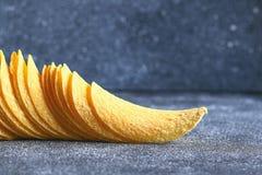 Ένας σωρός των τριζάτων τσιπ σε έναν γκρίζο σκοτεινό πίνακα snack στοκ εικόνες με δικαίωμα ελεύθερης χρήσης