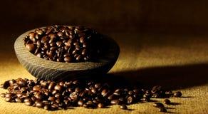 Ένας σωρός των φασολιών καφέ σε ένα κύπελλο συγκρατημένο στοκ εικόνα