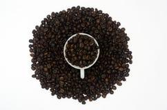 Ένας σωρός των φασολιών καφέ στο φλυτζάνι καφέ και στο υπόβαθρο επίσης στο άσπρο υπόβαθρο που απομονώνεται Στοκ Εικόνα