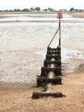 Ένας σωλήνας που οδηγεί έξω στη θάλασσα με το μέταλλο σημαδιών στην κορυφή groyne Στοκ Φωτογραφία