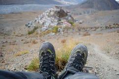 Ένας σόλο ταξιδιώτης με τα παπούτσια οδοιπορίας με το βασικό μοναστήρι στο υπόβαθρο Στοκ Φωτογραφία